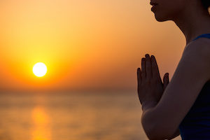 Profile of serene young woman relaxing on the beach meditating with hands in Namaste gesture at sunset or sunrise close up